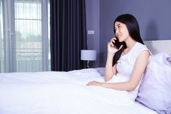 Femme parlant sur le téléphone portable sur le lit dans la chambre à coucher Photographie stock