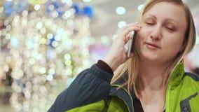 Femme parlant sur un smartphone, gêné et timide Elle se tient dans le mail, parmi une ampoule hors focale clips vidéos