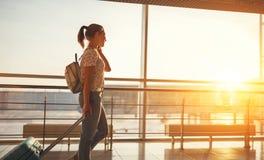 Femme parlant sur voler de attente de téléphone à l'aéroport à la fenêtre Images libres de droits