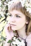 Femme parmi des fleurs Images stock