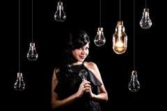 Femme parmi les ampoules photographie stock