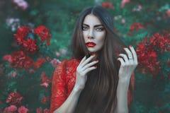 Femme parmi les fleurs avec de longs cheveux photographie stock libre de droits