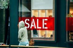Femme passant devant la grande fenêtre du magasin de luxe Photographie stock libre de droits