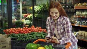 Femme passant en revue sa liste d'achats sur son smartphone image stock