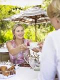 Femme passant la tasse de thé à l'ami au ? extérieur du CAM Image libre de droits