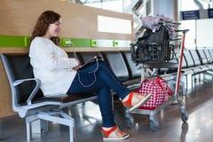 Femme passant le temps avec le PC de comprimé dans le salon d'aéroport Photos libres de droits