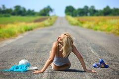 Femme passionné s'asseyant sur la route Images libres de droits