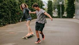 Femme patinant sur un terrain de basket avec l'ami Image stock