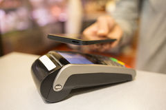 Femme payant avec la technologie de NFC au téléphone portable, dans le supermarché photographie stock libre de droits