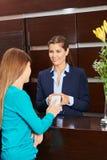 Femme payant avec le smartphone à la réception d'hôtel photos stock