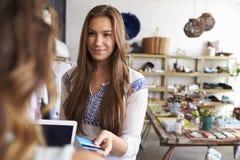 Femme payant l'employé de magasin avec la carte de crédit dans une boutique photo libre de droits