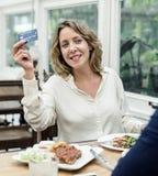 Femme payant le déjeuner avec la carte de crédit au restaurant Photographie stock libre de droits