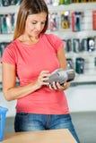Femme payant par Smartphone dans le magasin de matériel photo stock