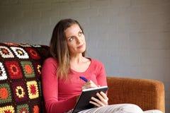 Femme pensant et prenant des notes dans le livre Images libres de droits