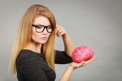 Femme pensant et tenant le faux cerveau Photographie stock libre de droits