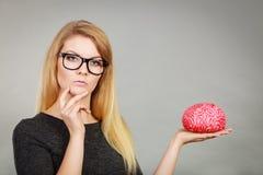 Femme pensant et tenant le faux cerveau Images stock
