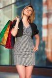 Femme pensif avec des sacs à provisions. Photographie stock libre de droits