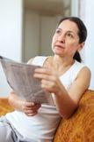 Femme pensive avec le journal Photo stock