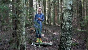 Femme perdue de sourire de récolteuse de champignon tenant le téléphone portable avec des généralistes dans la forêt clips vidéos