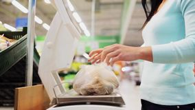 Femme pesant la pomme de terre sur l'échelle à l'épicerie clips vidéos