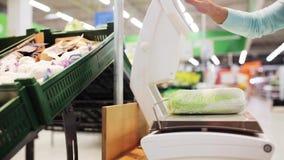 Femme pesant le chou de chine sur l'échelle à l'épicerie banque de vidéos