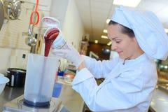 Femme pesant le liquide dans le récipient image stock