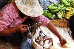 Femme pesant le poisson frais sur une vieille échelle, marché local Images libres de droits