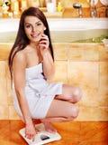 Femme pesée sur des échelles de plancher Photographie stock libre de droits