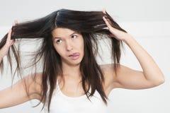 Femme peu satisfaite dans la condition ses longs cheveux image libre de droits