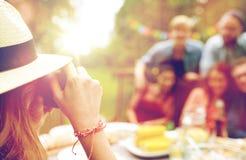 Femme photographiant des amis à la réception en plein air d'été Photo stock