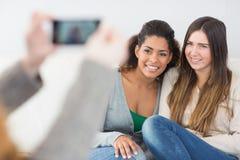 Femme photographiant des amis avec le smartphone Photo libre de droits