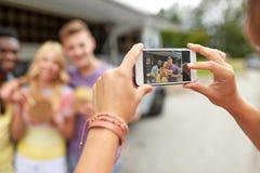 Femme photographiant des amis mangeant au camion de nourriture Photo stock