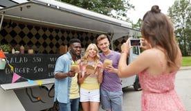 Femme photographiant des amis mangeant au camion de nourriture Photo libre de droits