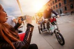 Femme photographiant des amis sur le tour de tricycle Images libres de droits