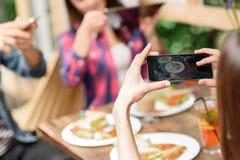 Femme photographiant la nourriture par le smartphone Images libres de droits