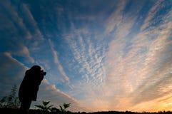 Femme photographiant le lever de soleil Photos stock