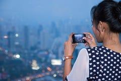 Femme photographiant une vue de Bangkok crépusculaire Photographie stock libre de droits
