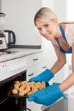 Femme plaçant des biscuits en four photo stock