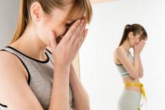 femme pleurante devant le miroir avec la bande de mesure sur la taille Photographie stock libre de droits