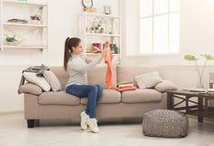 Femme pliant les T-shirts propres à la maison photo stock