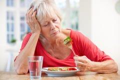 Femme plus âgé malade essayant de manger Photo stock