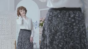 Femme plus âgée élégante mignonne regardant dans le miroir, examinant sa réflexion La dame regardant sa nouvelle longue jupe dans banque de vidéos