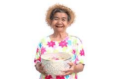 Femme plus âgée asiatique heureuse tenant la cuvette avec la fleur sur le fond blanc Image stock