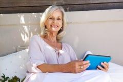 Femme plus âgée attirante s'asseyant dehors avec le comprimé numérique Photographie stock