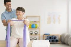 Femme plus âgée de aide de sourire de physiothérapeute Photo stock