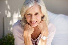 Femme plus âgée de sourire avec la main dans des mains dehors Photographie stock