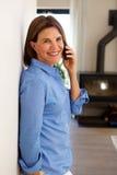 Femme plus âgée de sourire parlant sur le téléphone portable et la maison photo libre de droits
