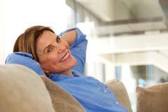 Femme plus âgée de sourire s'asseyant sur le sofa à la maison images stock
