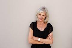 Femme plus âgée de sourire se penchant sur le mur avec des bras croisés Image libre de droits