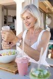Femme plus âgée en bonne santé mangeant au café extérieur Photos stock